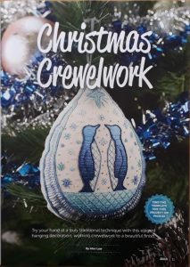 Photo of my project in Stitch magazine. The design is of 2 penguins in a snow scene made up into a decoration hanging from a Christmas tree.