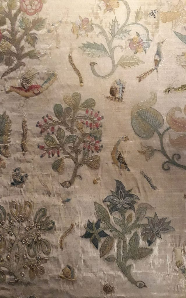 Showing a number of large floral motifs and small animal motifs. The colours in this section of the cloth are the least faded.
