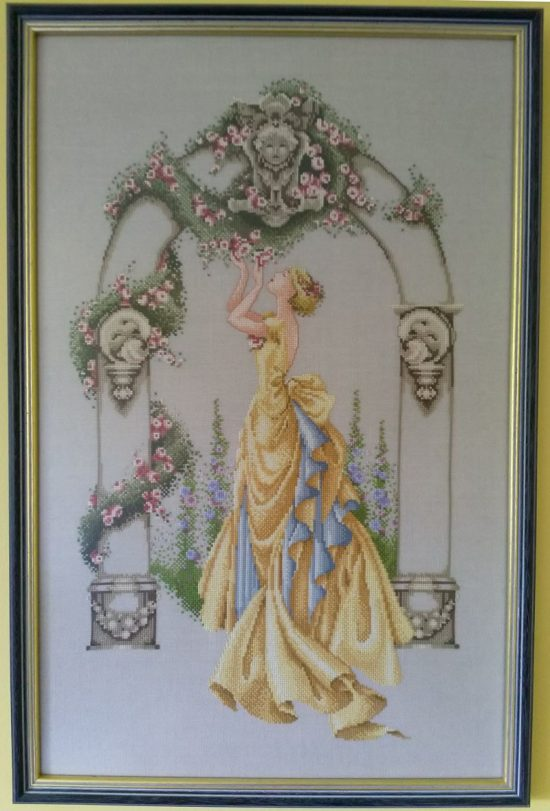 Cross stitch picture of a lady wearing a yellow dress in a rose arch