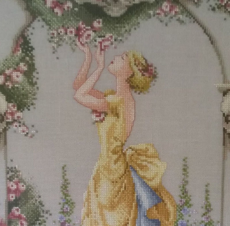 cross stitch of a lady smelling roses