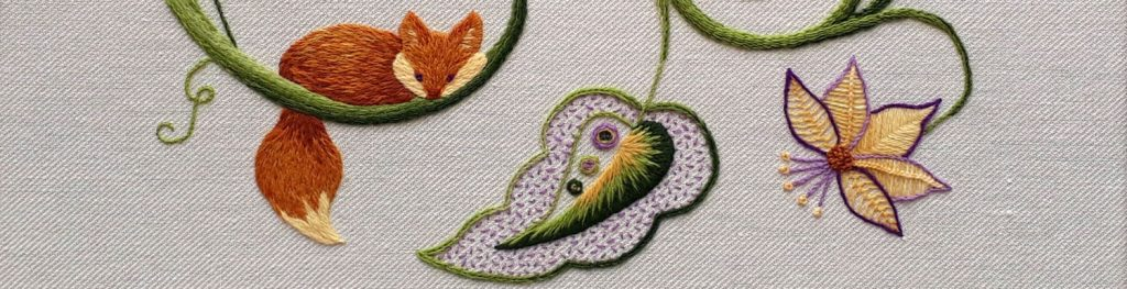Crewel embroidery featuring a fox, leaf and flower