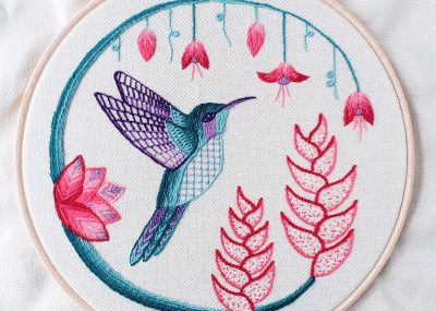 Crewelwork embroidery of a green and purple hummingbird in flight around pink flowers.