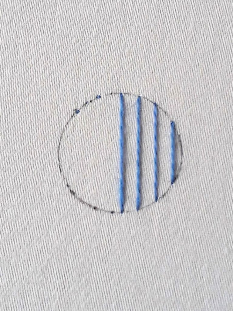Image showing the right side of a circle worked in long vertical stitches.