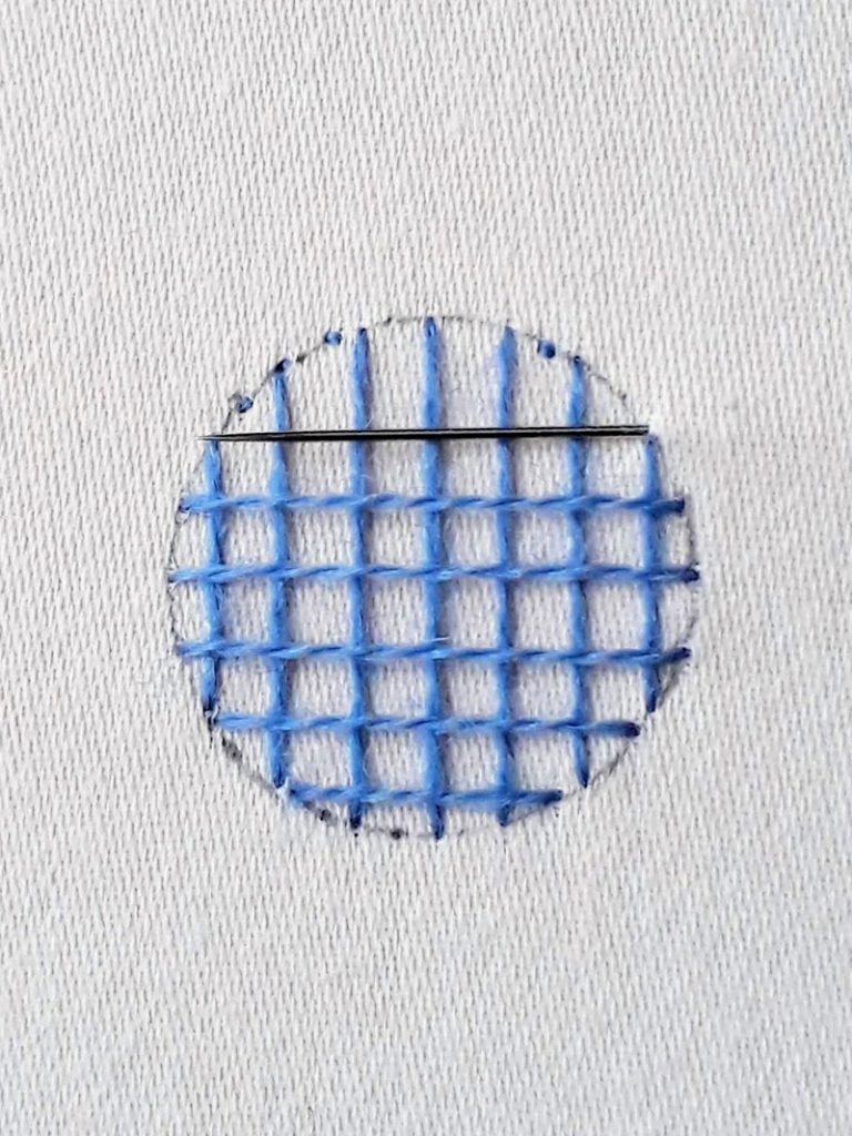 Image showing how I check the positioning of my next stitch by laying the needle along the fabric parallel to previous stitches.