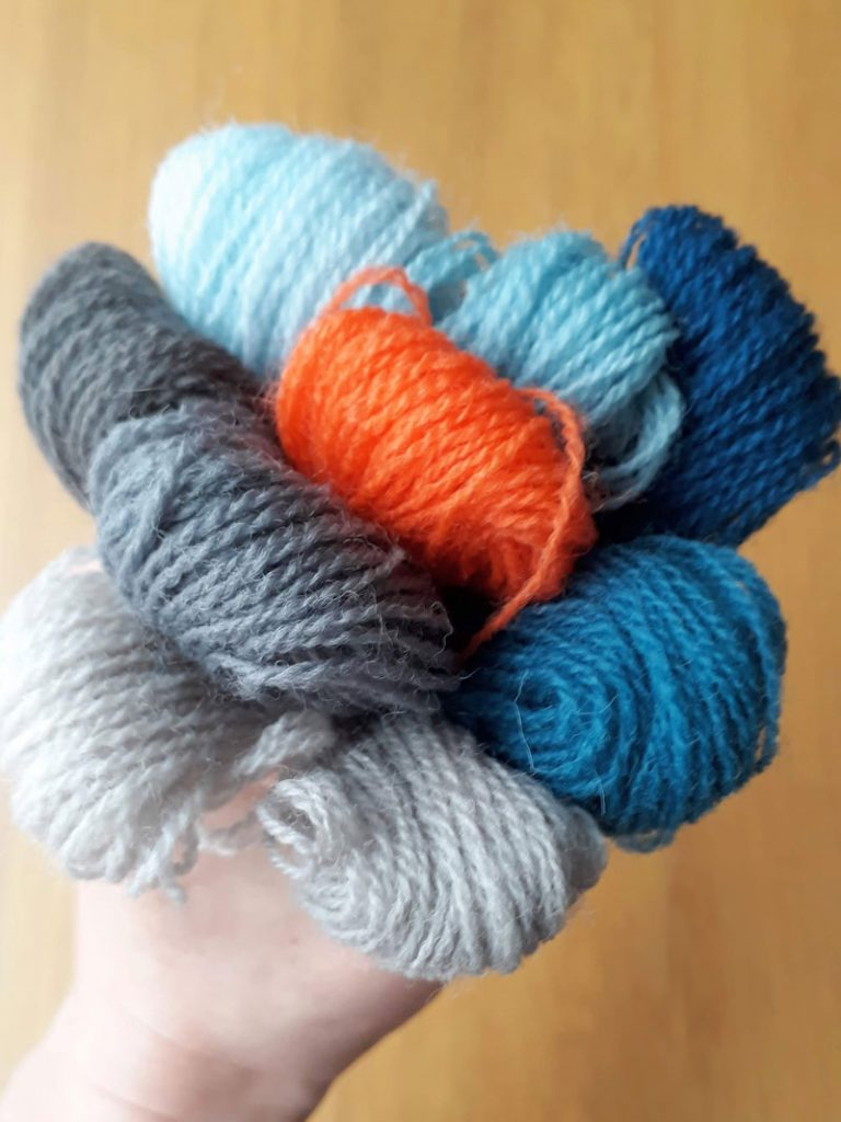 Photo of a bundle of blue, grey and orange threads held in a hand.