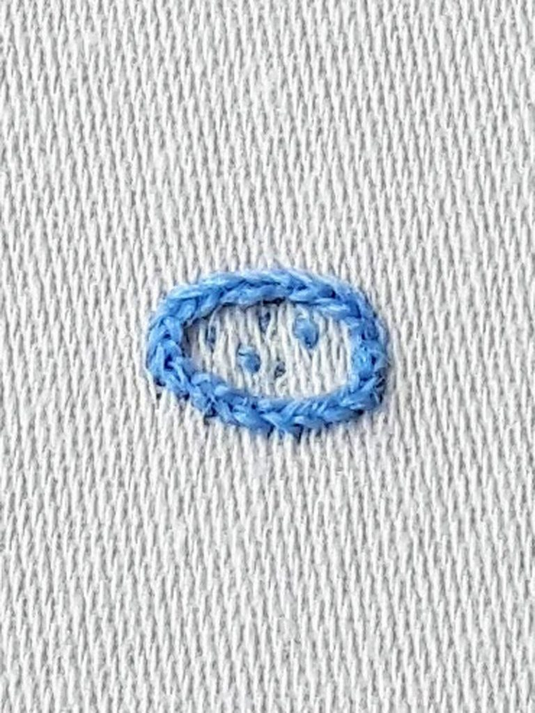 A ring of split stitch in light blue thread.