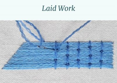 Long parallel stitches are being secured in place with perpendicular rows of couching.