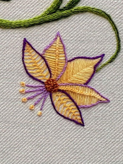 A crewel embroidery yellow and purple flower.