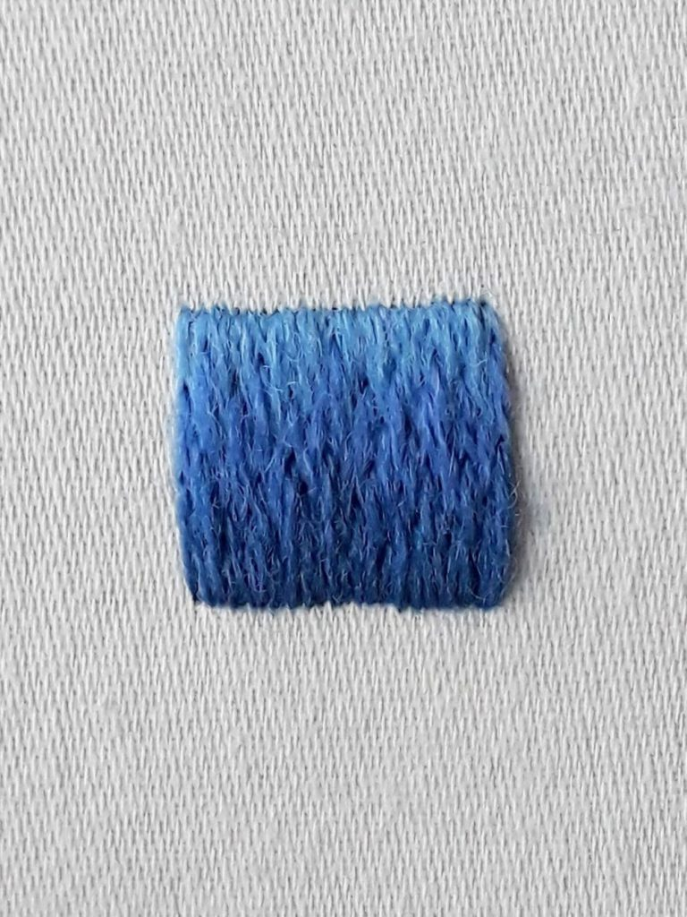A square worked in long and short stitch and crewel wools. It is light blue at the top and shades down to dark blue at the base.