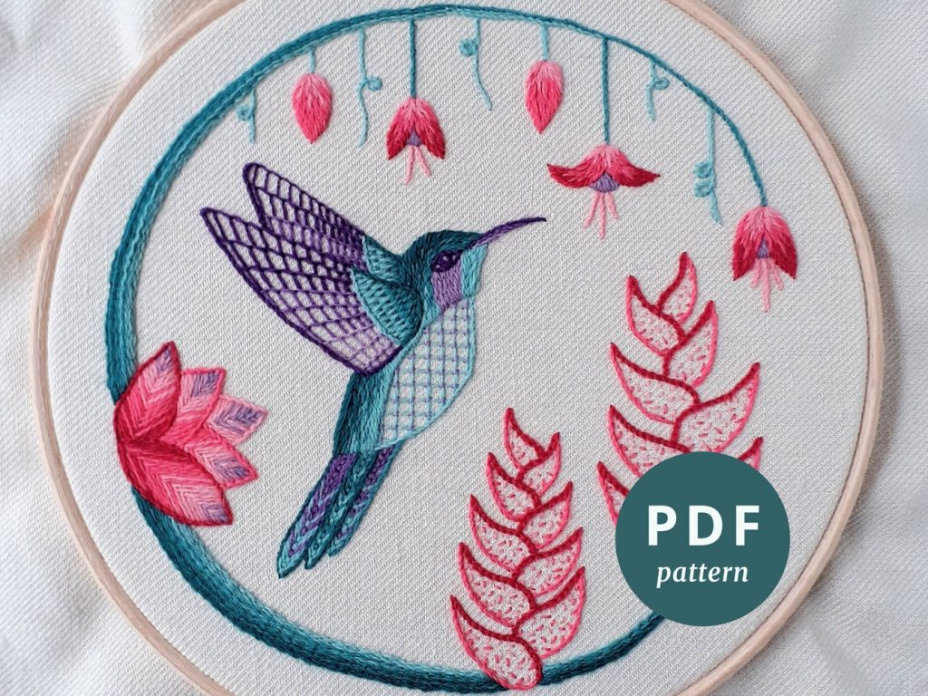 Crewelwork embroidery of a green and purple hummingbird surrounded by pink flowers.