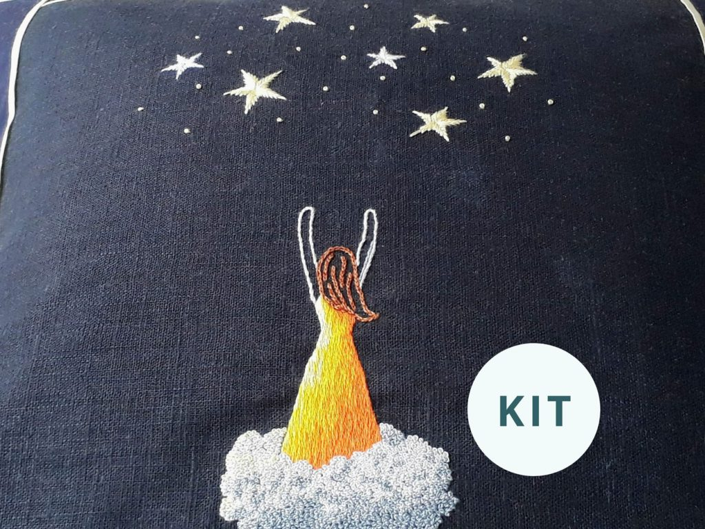 Embroidery on navy blue fabric of a woman wearing an orange dress, standing on a cloud, reaching up to stars above her.