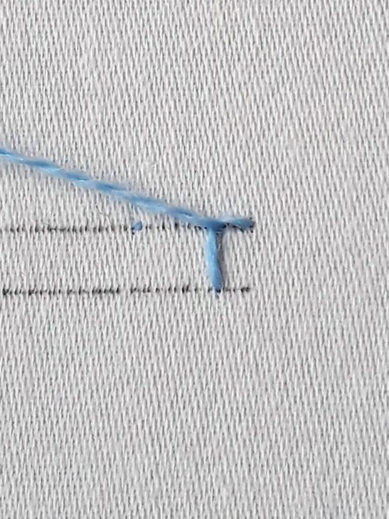First buttonhole stitch complete, the working thread is being pulled to the side so that the stitch forms an L shape.