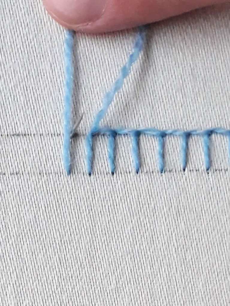 Holding my thread along the fabric where I want my stitch to be, then bringing up my needle next to it.