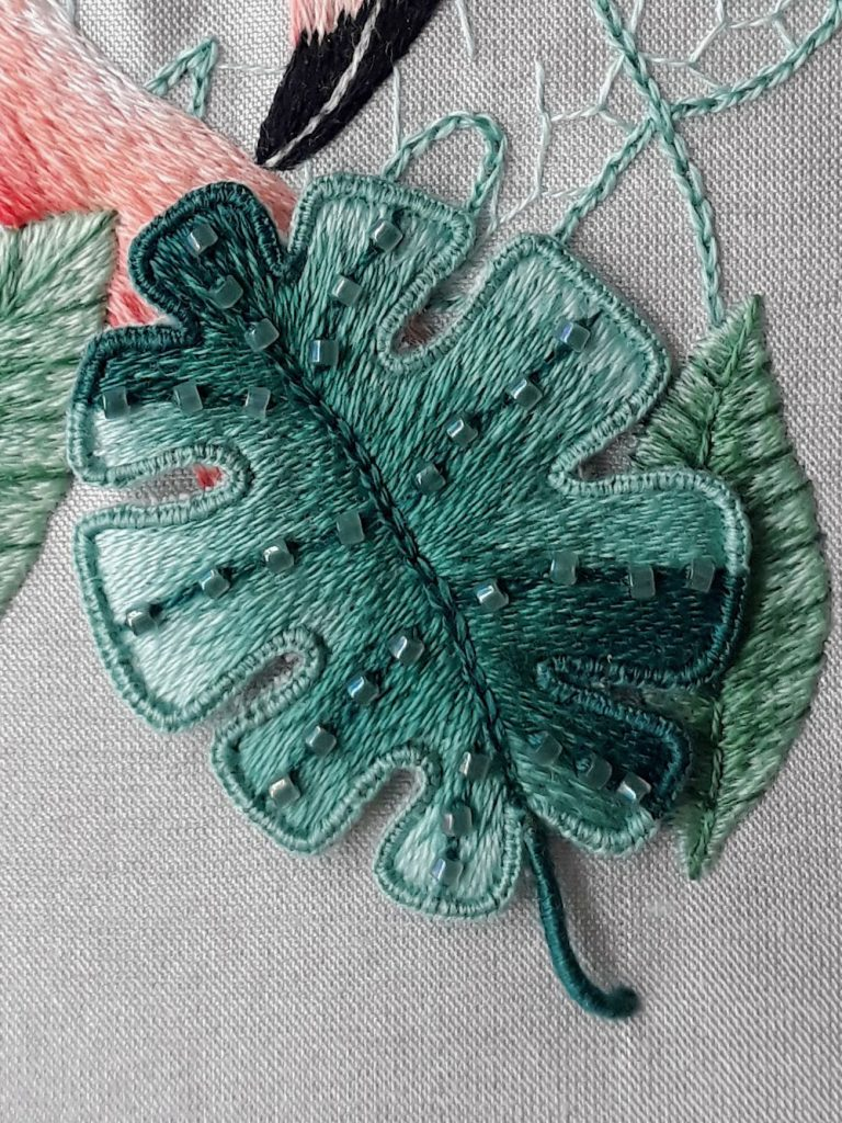 Close up of a stumpwork leaf worked in shades of green with a buttonhole stitch edge.