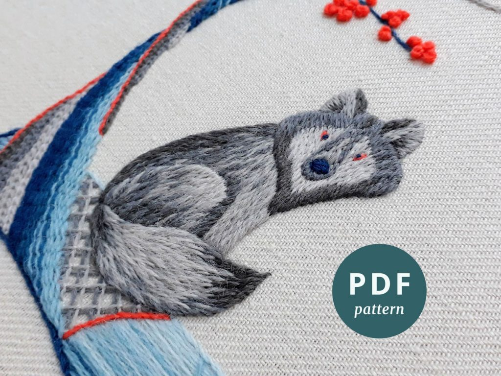 Crewelwork embroidery of a wolf sitting next to a tree, worked in shades of blue and grey with a little orange.