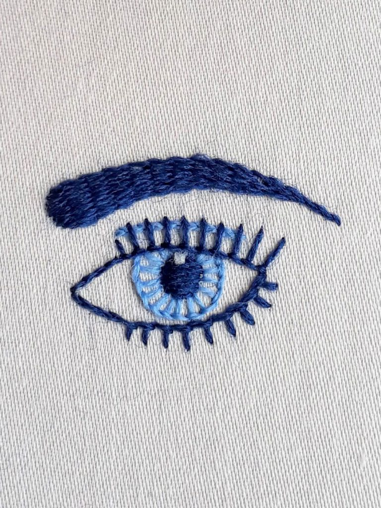 Eye embroidery pattern stitched in light and dark blue crewel wool.