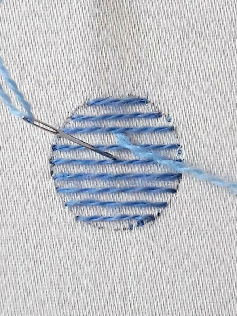 Working the first stitch by angling my needle under one of the long stitches.