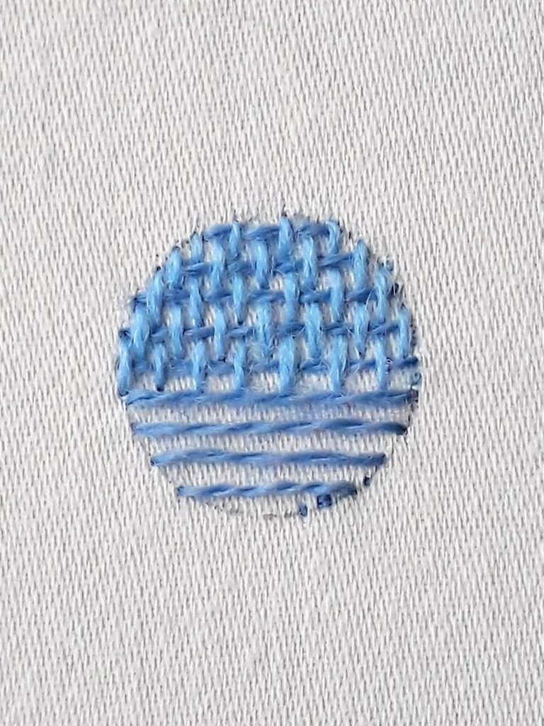 A circle where the top half has been fully stitched with burden stitch. The lower half is covered with long horizontal stitches.