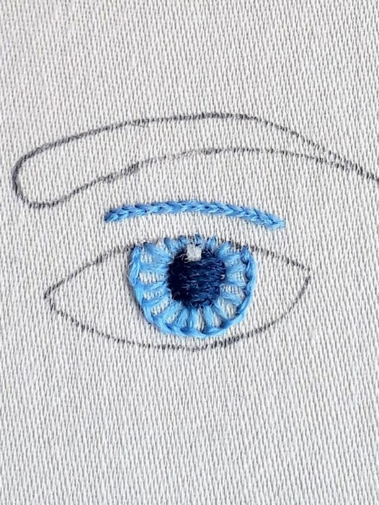 Eye embroidery in progress with the eyelid crease line and eye iris stitched in light blue. Pupil stitched in dark blue with a highlight stitched in white.