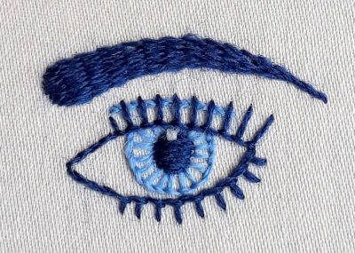 Eye embroidery pattern stitched in light and dark blue crewel wools.