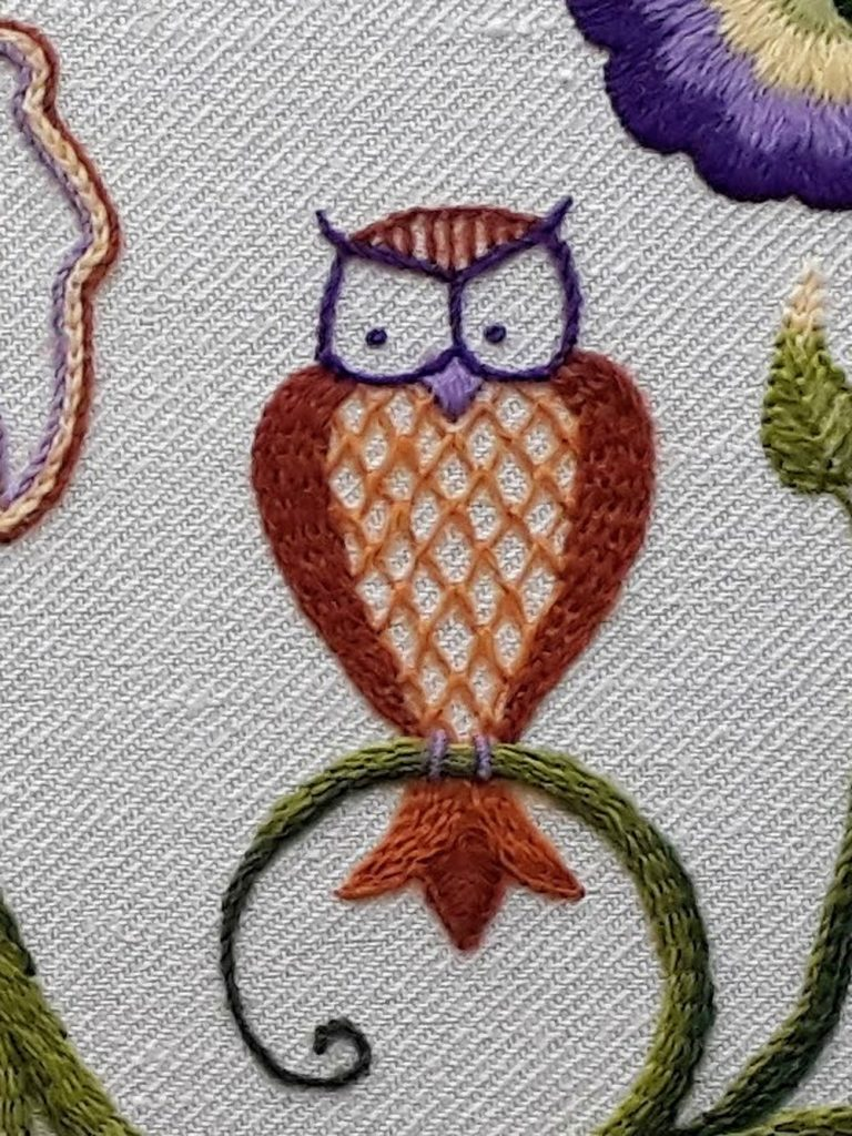 An owl stitched in the Jacobean crewelwork embroidery style. His wings are burden stitch going around a curve.