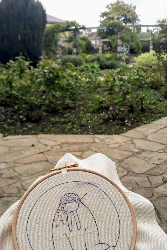 Foreground shows a walrus embroidery being stitched, in the background is the walled garden.