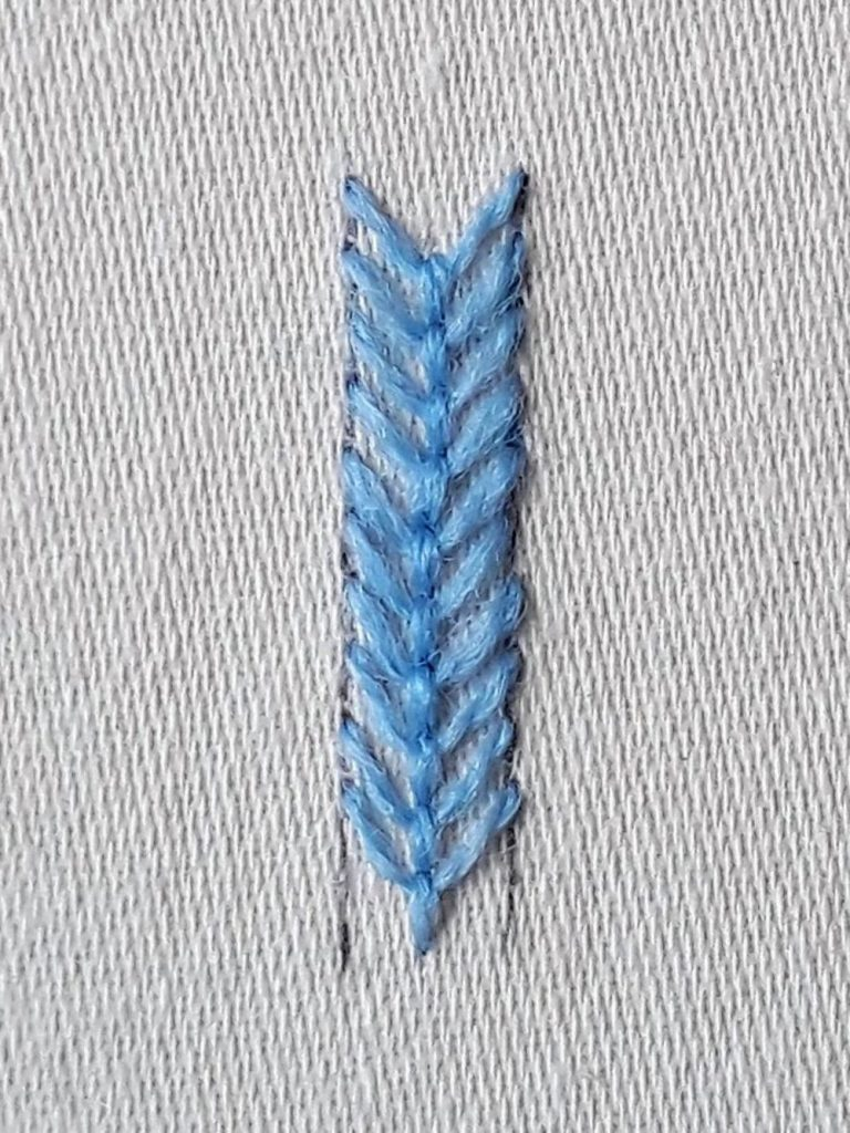 A completed line of fly stitch in blue crewel wool.